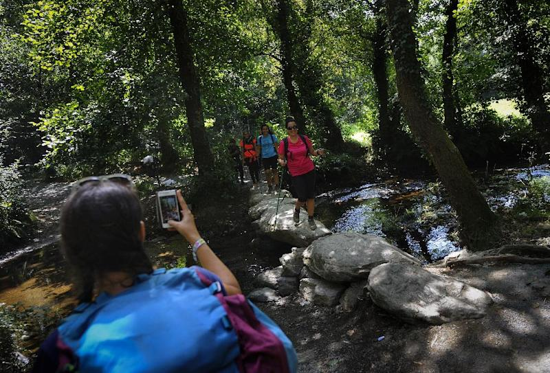 A pilgrim takes pictures of her friends with a smartphone as they cross the Catasol river on the Way of Saint James, close to the village of Melide, some 60 km from Santiago de Compostela, on August 21, 2014 (AFP Photo/Miguel Riopa)