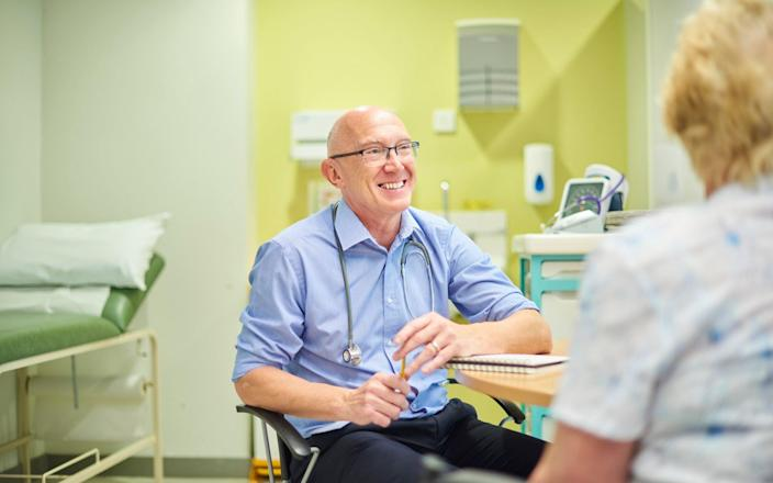 Senior male GP at his desk chatting with a patient - Getty Images