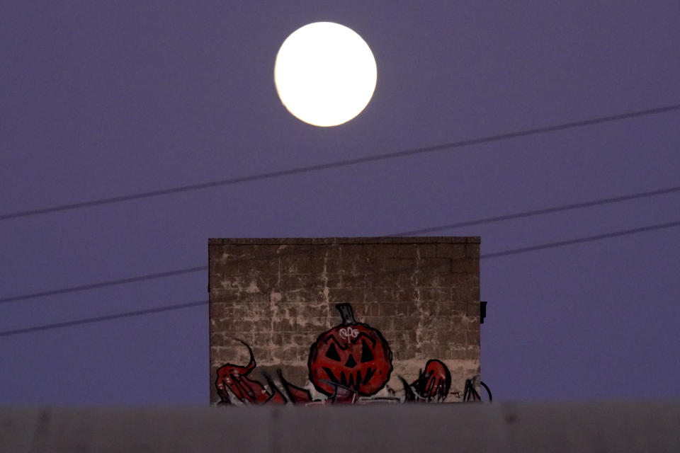 The nearly full moon rises beyond Halloween artwork painted on a building Thursday, Oct. 29, 2020, in Kansas City, Mo. (AP Photo/Charlie Riedel)