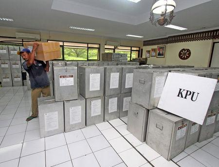 A worker carries a box with ballots during preparations for the second round of an election for Jakarta's governor in Jakarta