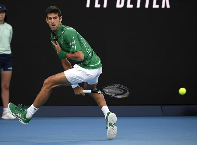 Serbia's Novak Djokovic plays a shot between his legs to Austria's Dominic Thiem during the men's singles final at the Australian Open tennis championship in Melbourne, Australia, Sunday, Feb. 2, 2020. (AP Photo/Andy Brownbill)