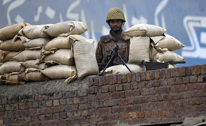 A Pakistani soldier stands guard at a checkpoint near the Kot Lakhpat Jail on the outskirts of Lahore on December 22, 2014, following a government decision to hang convicted militants (AFP Photo/Arif Ali)
