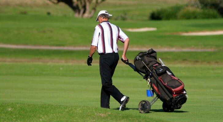 A retired man strolls down a golf course fairway.