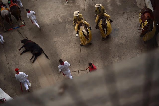 <p>A Jandilla ranch bull is dragged out of the bullring during a bullfight at the San Fermin Fiestas in Pamplona, Spain, July 11, 2017. (Photo: Alvaro Barrientos/AP) </p>