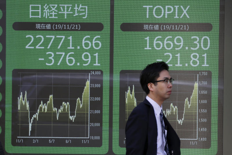 A man walks by an electronic stock board of a securities firm in Tokyo, Thursday, Nov. 21, 2019. Shares skidded Thursday in Asia after moderate declines on Wall Street as anxious mounted over the possibility the U.S. and China may not reach a trade deal before next year. (AP Photo/Koji Sasahara)