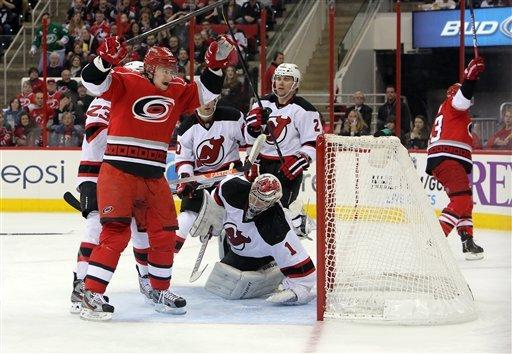 Carolina Hurricanes' Jussi Jokinen, left, of Finland, celebrates a goal by teammate Jeff Skinner, right, against New Jersey Devils' goalie Johan Hedberg (1), of Sweden, and defender Marek Zidlicky (2), of the Czech Republic, during the second period of an NHL hockey game in Raleigh, N.C., Saturday, March 9, 2013. (AP Photo/Ted Richardson)
