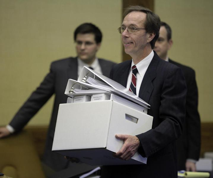 Defense attorney Peter Messitt carries a box load of exhibits towards the bench in Montgomery County Circuit Court in Christiansburg, Va. on Wednesday March 14 2012. Jurors began deliberating Wednesday over a lawsuit filed by the parents of two students slain in the 2007 Virginia Tech massacre claiming school officials botched their response when the first reports came in that a gunman was on campus. Attorneys for the university have countered that there was no way to anticipate the man who committed those first two killings April 16 in a dormitory would carry out the deadliest mass shooting in modern U.S. history. (AP Photo/The Roanoke Times, Matt Gentry)