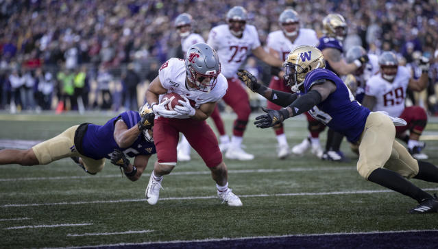 Washington State wide receiver Brandon Arconado runs with the ball after making a catch as Washington defensive back Myles Bryant and linebacker Edefuan Ulofoshio move in for a tackle during an NCAA college football game, on Friday, Nov. 29, 2019 in Seattle. (AP Photo/Stephen Brashear)