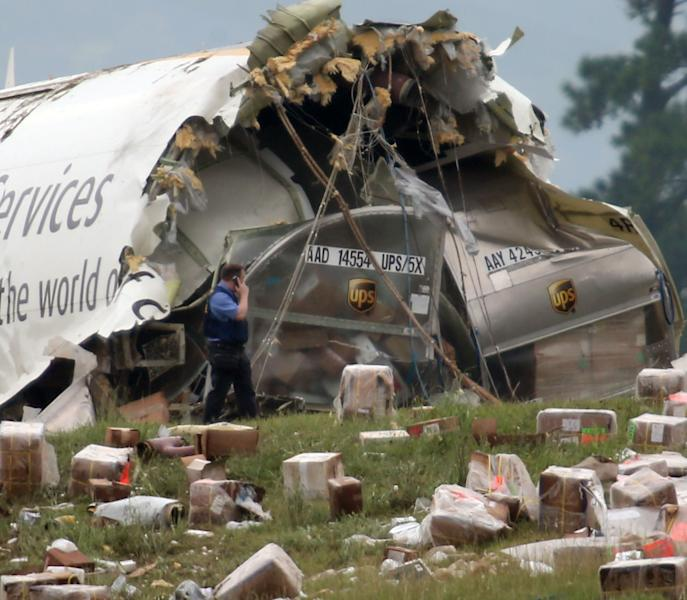 A postal inspector officer looks over the debris of an UPS Airbus A300 cargo plane after it crashed on approach at Birmingham-Shuttlesworth International Airport this morning Wednesday, Aug. 14, 2013 in Birmingham, Ala. A UPS cargo plane crashed and burned Wednesday morning on the outskirts of an Alabama airport, killing two crew members and scattering boxes and charred debris across a grassy field, officials said. (AP Photo/Hal Yeager)