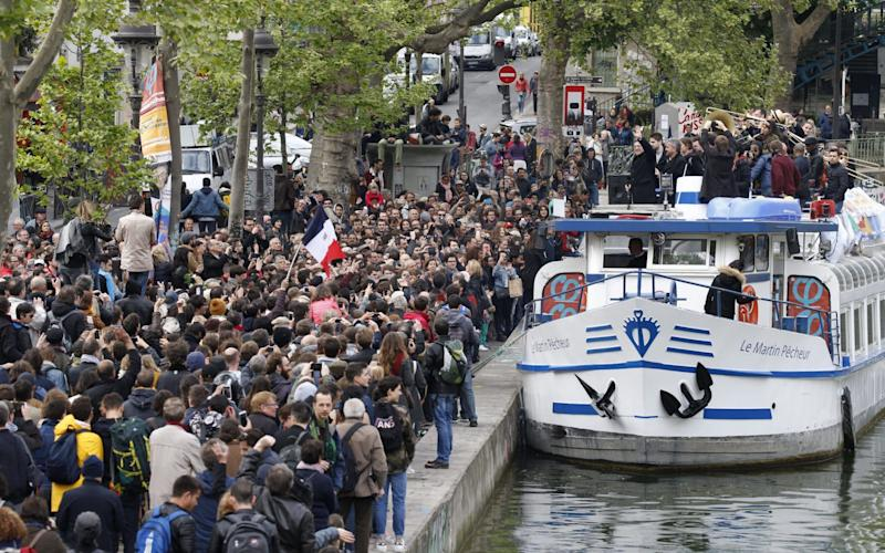 Communist-backed French presidential candidate Jean-Luc Melenchon waves, at supporters as he cruises on a barge on the canal de l'Ourcq in Paris - Credit:  CHARLES PLATIAU/Reuters