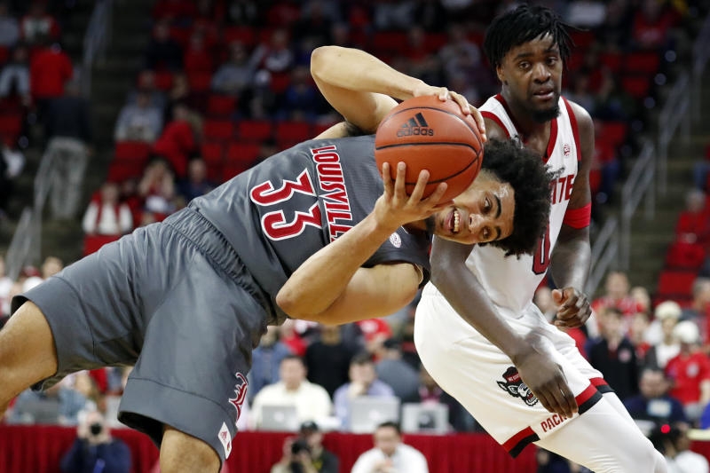 Louisville's Jordan Nwora (33) tries to stay in bounds after battling for the ball with North Carolina State's DJ Funderburk (0) during the second half of an NCAA college basketball game in Raleigh, N.C., Saturday, Feb. 1, 2020. (AP Photo/Karl B DeBlaker)