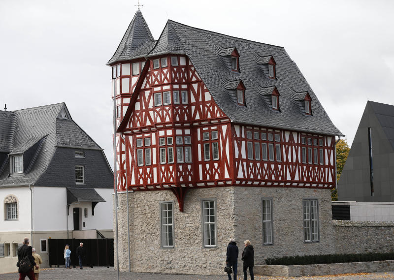 """FILE - In this Oct. 17, 2013 file picture people watch a part of the residence of Franz-Peter Tebartz-van Elst, Bishop, in Limburg, Germany. Pope Francis on Wednesday, March 26, 2014 permanently removed a German bishop from his Limburg diocese after his 31 million-euro ($43-million) new residence complex caused an uproar among the faithful. Francis had temporarily expelled Monsignor Franz-Peter Tebartz-van Elst from Limburg in October pending a church inquiry into the affair. The Vatican said Wednesday that the inquiry found that Tebartz-van Elst could no longer exercise his ministry and that Francis had accepted his resignation, which was originally offered Oct. 20. A replacement, Monsignor Manfred Grothe, currently an auxiliary bishop in Paderborn, will take over, the Vatican said, citing a statement from the diocese. It said Tebartz-van Elst would get a new job """"at the opportune time. (AP Photo/Frank Augstein, FILES)"""