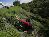 Volunteers use shovels as they search an area for the bodies of missing persons on the outskirts of Cuautla, Mexico, Tuesday, Oct. 12, 2021. The government's registry of Mexico's missing has grown more than 20% in the past year and now approaches 100,000. (AP Photo/Fernando Llano)