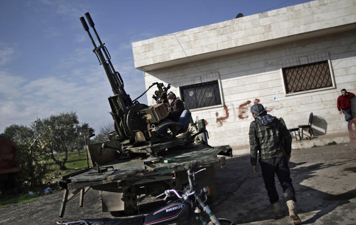 In this Friday, Dec. 14, 2012 photo, a Syrian rebel checks an anti-aircraft weapon, in Maaret Misreen, near Idlib, Syria. The new Syrian rebel chief, a defected army general who spent months in exile, says he has begun operating inside Syria to unite autonomous anti-regime militias for what he hopes will be the final push against President Bashar Assad. (AP Photo/Muhammed Muheisen)