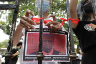 A demonstrator ties a red ribbon on a gate of the Department of Justice to symbolize their protest while holding a picture of U.S. Marine Lance Cpl. Joseph Scott Pemberton during a rally in Manila, Philippines on Thursday, Sept. 3, 2020. A Philippine court has ordered the early release for good conduct of Pemberton convicted in the 2014 killing of a transgender Filipino which sparked anger in the former American colony. (AP Photo/Aaron Favila)
