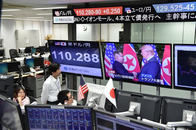 <p>Employees of a foreign exchange trading company in Tokyo watch live news of the summit in Singapore and the Japanese yen's exchange rate against the U.S. dollar on Tuesday. (Photo: Kazuhiro Nogi/AFP/Getty Images) </p>