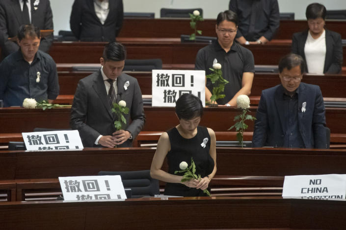 """Pro-democracy lawmakers pay a silent tribute to the man who fell to his death on Saturday evening after hanging a protest banner on scaffolding on a shopping mall, at the Legislative Council in Hong Kong, Wednesday, June 19, 2019. Hong Kong lawmakers are meeting for the first time in a week, after massive protests over an extradition bill that eventually was suspended. The placards with Chinese read """"Withdraw"""". (AP Photo/Kin Cheung)"""