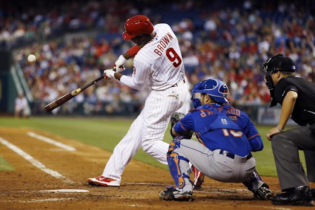 Philadelphia Phillies' Domonic Brown hits a three-run home run off New York Mets starting pitcher Rafael Montero during the fourth inning of a baseball game, Friday, May 30, 2014, in Philadelphia. At center is catcher Travis d'Arnaud and at right is umpire Cory Blaser. (AP Photo/Matt Slocum)