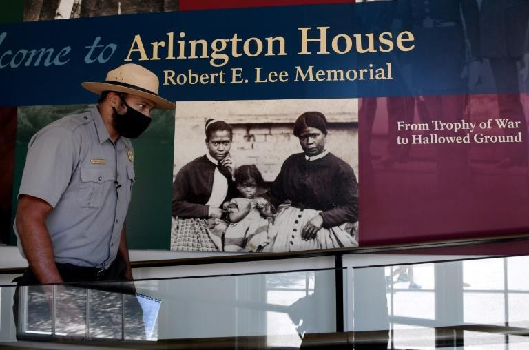 Park Ranger Aaron LaRocca walks past the entrance of Arlington House, featuring a photo believed to be of enslaved housekeeper Selina Gray and two of her daughters (AFP/Olivier DOULIERY)