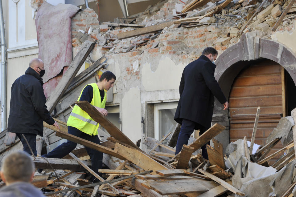 People walk through debris from buildings damaged in an earthquake in Petrinja, Croatia, Tuesday, Dec. 29, 2020. A strong earthquake has hit central Croatia and caused major damage and at least one death and some 20 injuries in the town southeast of the capital Zagreb. (AP Photo)