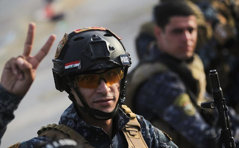 A member of the Iraqi federal police flashes the victory sign during a celebration in the Old City of Mosul, where the gruelling battle to retake Iraq's second city from Islamic State (IS) group fighters is now nearing its end, on July 2, 2017 (AFP Photo/AHMAD AL-RUBAYE)