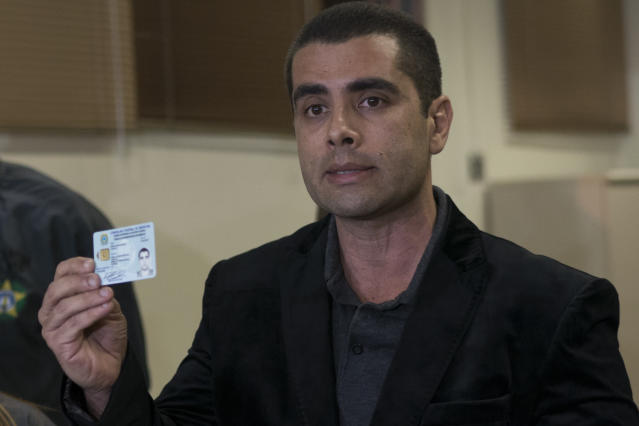 <em>The plastic surgeon shows his doctors licence as he speaks to the press (AP)</em>