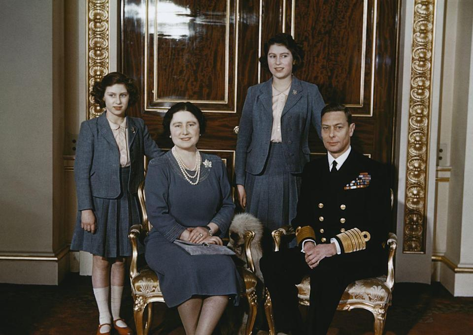 <p>Princess Margaret, Queen Elizabeth the Queen Mother, Princess Elizabeth, and King George VI pose for a family portrait at Buckingham Palace. The royal daughters match in gray blazers, pleated skirts, and peach button-down shirts.</p>