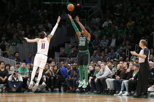 Boston Celtics guard Marcus Smart (36) launches a 3-point shot over Phoenix Suns guard Ricky Rubio (11) during the first half of an NBA basketball game, Saturday, Jan. 18, 2020, in Boston. (AP Photo/Mary Schwalm)