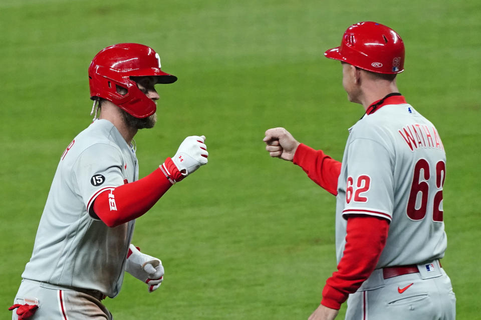 Philadelphia Phillies' Bryce Harper (3) celebrates with third base coach Dusty Wathan (62) as he rounds third base after hitting a home run in the sixth inning of a baseball game against the Atlanta Braves, Saturday, April 10, 2021, in Atlanta. (AP Photo/John Bazemore)