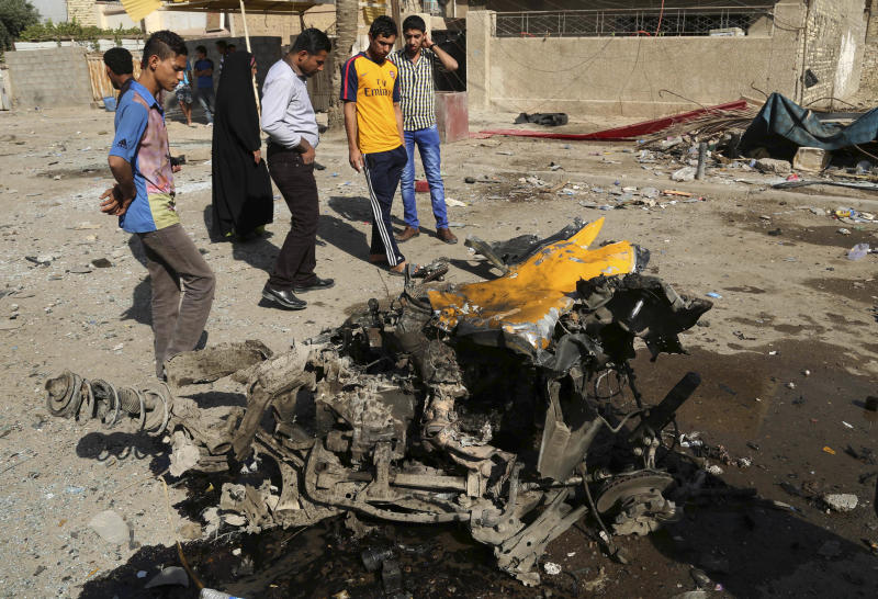 Citizens inspect the site of a car bomb attack in the capital's eastern Mashtal neighborhood, Iraq, Sunday, Oct. 27, 2013. Insurgents on Sunday unleashed a new wave of car bombs in Shiite neighborhoods of Baghdad, killing and wounding dozens of people, officials said. (AP Photo/ Khalid Mohammed)