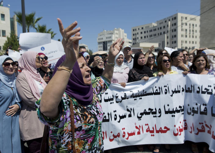 """Palestinian women hold a banner that reads, """"Palestinian Woman's General Union, we need a law to protect us and to protect the Palestinian family,"""" during a rally in front of the Prime Minister's office, in the West Bank city of Ramallah, Monday, Sept. 2. 2019. Hundreds of Palestinian women protested in front of the prime minister's office to demand an investigation into the death of Israa Ghrayeb, a 21-year-old woman whom many suspect was the victim of a so-called honor killing. (AP Photo/Nasser Nasser)"""