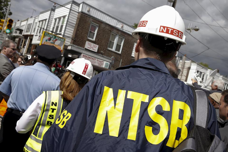 U.S. National Transportation Safety Board officials stand on the sidelines of a news conference near the site of a derailed Amtrak train in Philadelphia, Pennsylvania May 13, 2015. The U.S. National Transportation Safety Board has opened a broad investigation into the cause of the train derailment north of Philadelphia that left at least six people dead, an official for the agency said on Wednesday. REUTERS/Mike Segar
