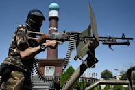 A Taliban fighter seen in front of Massoud Circle, a monument in Kabul named after the famed guerrilla commander (AFP/Aamir QURESHI)