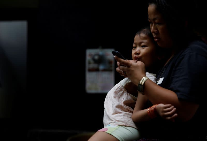 Nepali housewife Shiba Kala Limbu uses her mobile phone while her five-year-old daughter Masim Limbu sits on her lap in Kathmandu