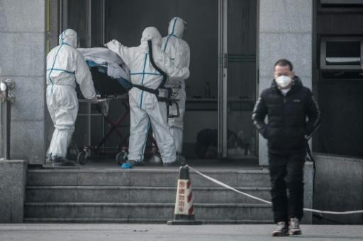 Medical workers carry a patient into a hospital for patients infected with the new coronavirus strain in Wuhan, China