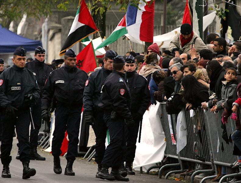Policemen walk past the people gathered outside the Percy military hospital in the Paris southwestern suburb of Clamart, November 11, 2004, after Yassser Arafat died overnight at the age of 75 (AFP Photo/Joel Saget)