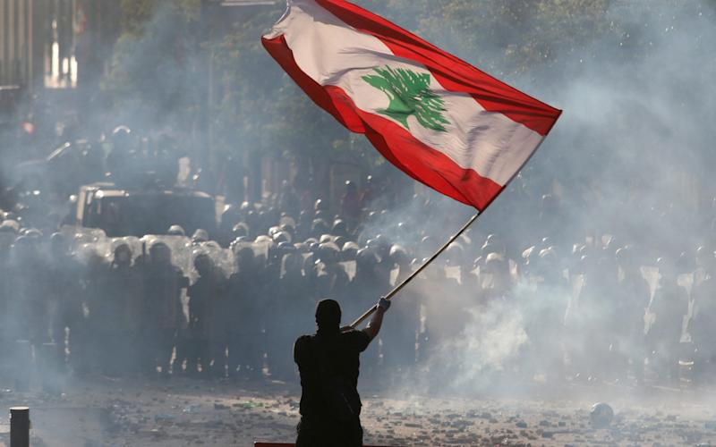 A demonstrator waves the Lebanese flag in front of riot police during a protest in Beirut - REUTERS