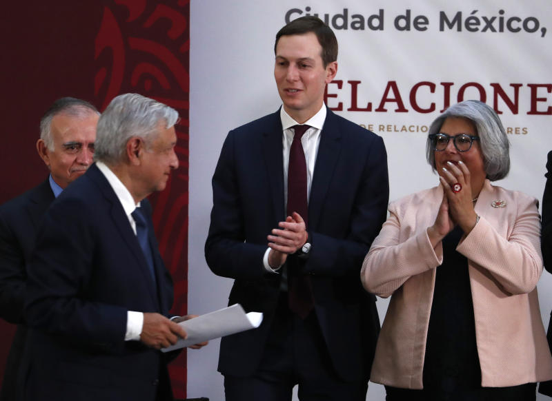 Mexico's President Andres Manuel Lopez Obrador, left, walks after delivering his remarks, as White House senior adviser Jared Kushner, center, and Mexico Economy Minister Graciela Márquez, right, applaud, after a ceremony to sign an update to the North American Free Trade Agreement, at the national palace in Mexico City, Tuesday, Dec. 10. 2019. (AP Photo/Marco Ugarte)