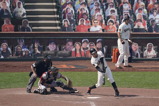 San Francisco Giants' Wilmer Flores, bottom right, hits a double in front of Arizona Diamondbacks catcher Stephen Vogt during the sixth inning of a baseball game in San Francisco, Sunday, Sept. 6, 2020. (AP Photo/Jeff Chiu)