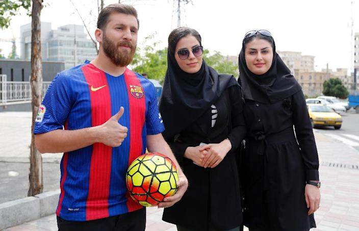 Reza Parastesh, a doppelganger of Barcelona and Argentina's footballer Lionel Messi, poses for a picture with fans in a street in Tehran on May 8, 2017 (AFP Photo/ATTA KENARE)