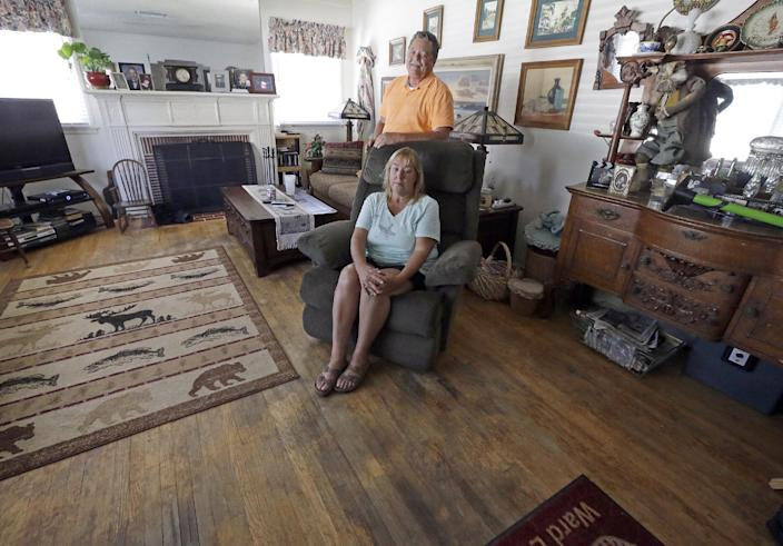 In this Aug. 27, 2013 photo, Madeleine and Jerry Bosco pose in their living room, with mostly inherited or thrift shop furnishings and a hardwood floor in need of refinishing or replacement, in the Tujunga area of Los Angeles. Now, five years after the recession, when Jerry's pay was cut 15 percent and their home lost some of its value, they've had to cut back on necessities such as food, utilities, home repairs and new appliances, as well as extras such as weekend trips and dinners out. (AP Photo/Reed Saxon)