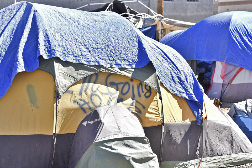 Tents for homeless at the Lots in downtown Phoenix have tarps or blankets draped over them on June 24, 2020, for an added layer of relief from the heat. Homeless people are among the most vulnerable populations in the COVID-19 pandemic, yet they're largely invisible victims. Very little is known about how they're faring. The U.S. Department of Housing and Urban Development, which oversees homeless programs, has not required its national network of providers to gather infection or death data, even though homeless people, unlike other high-risk groups such as nursing home residents, interact more with the public. (Steve Carr/Human Services Campus and the Howard Center For Investigative Journalism via AP)