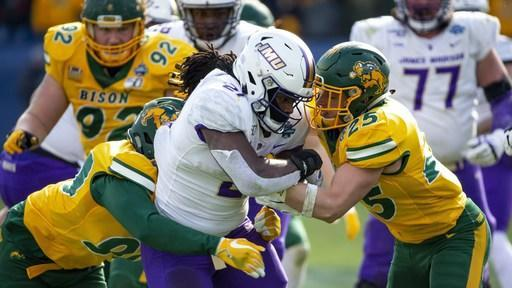 James Madison running back Latrele Palmer (21) is tackled by North Dakota State safety Michael Tutsie (25) and defensive end Tony Pierce (90) during the second half of the FCS championship NCAA college football game, Saturday, Jan. 11, 2020, in Frisco, Texas. (AP Photo/Sam Hodde)