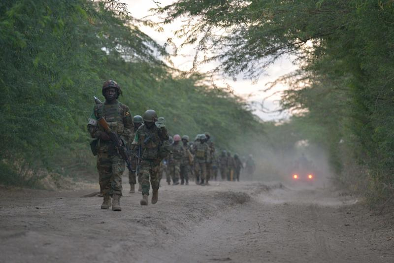 Ugandan soldiers of the African Union Mission in Somalia walk towards the town of Qoryooley, Somalia, on March 22, 2014