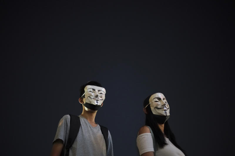 Protesters wear masks during a protest in Hong Kong, Friday, Oct. 18, 2019. Hong Kong pro-democracy protesters are donning cartoon/superhero masks as they formed a human chain across the semiautonomous Chinese city, in defiance of a government ban on face coverings. (AP Photo/Felipe Dana)