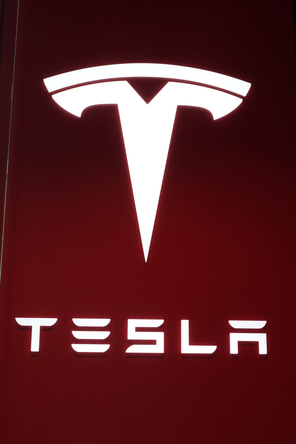 The Tesla logo is displayed at the Tesla Gallery on Feb. 24, 2021, in Troy, Mich. Opinion polls show that most Americans would consider an EV if it cost less, if more charging stations existed and if a wider variety of models were available. The models are coming, but they may roll out ahead of consumer tastes. And that could spell problems for the U.S. auto industry, which is sinking billions into the new technology with dozens of new vehicles on the way. (AP Photo/Carlos Osorio)