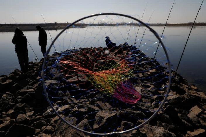 FILE PHOTO: Chinese men fish as watchtowers are seen on the North Korean side of the Yalu River just north of Dandong, in China's Liaoning province