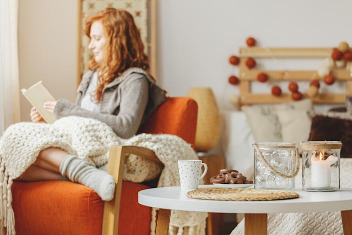 Woman with red hair sitting on chair with blanket and surrounded by candles in a cozy space