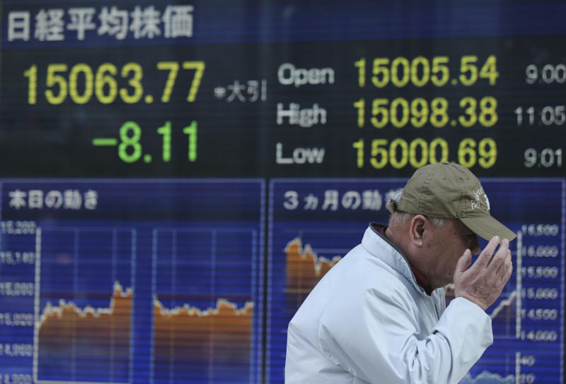 A man walks by an electronic stock board of a securities firm showing Tokyo's Nikkei 225 that slipped 8.11 points, or 0.05 percent to close at 15,063.77 in Tokyo, April 4, 2014. Asian stock markets were little changed Friday after the European Central Bank refrained from further easing of monetary policy and investors looked to the upcoming U.S. jobs report for a new trading cue. (AP Photo/Eugene Hoshiko)