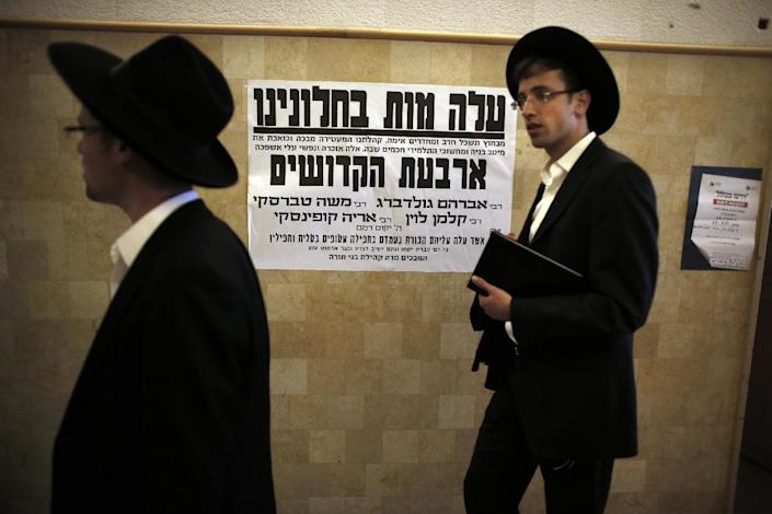 Ultra Orthodox Jews walk on November 19, 2014, past a poster in a synagogue in Jerusalem in memory of the five Israeli worhipers who were killed at the site the day before by two Palestinians (AFP Photo/Thomas Coex)